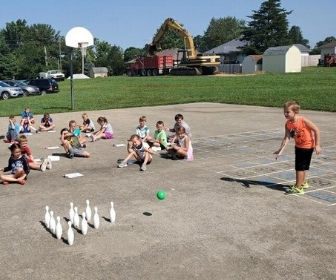 Students playing bowling in parking lot to learn math skills