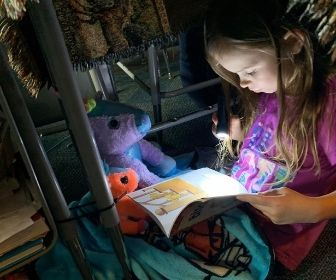 Student reading with a flashlight